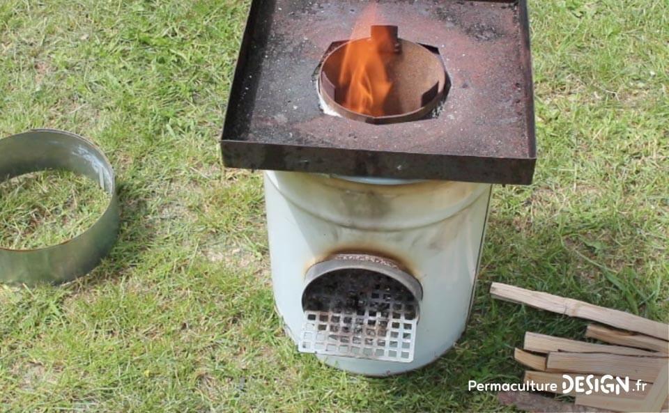 La technique du rocket stove est ici adaptée pour faire un barbecue ou un réchaud de plein air très efficace.
