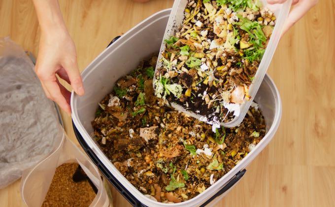 Remplissage du seau de compost bokashi avec des déchets de cuisine coupés en petits morceaux.